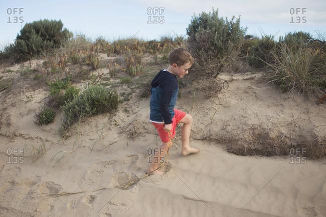 Little boy walking on sandy beach hill