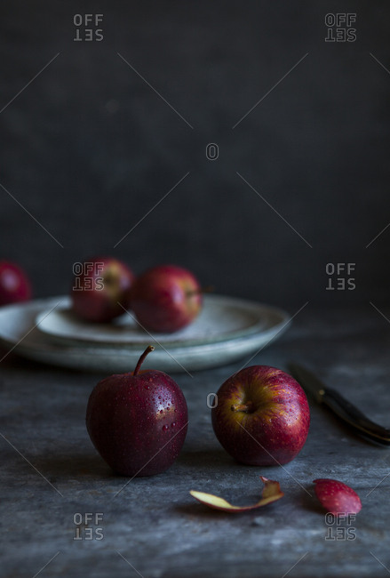 Red apples being sliced on a dark table