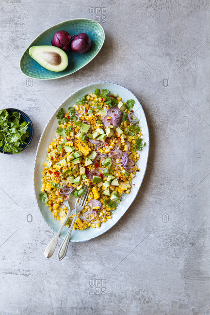 Mixed corn salad with avocados, onions and herbs on the side