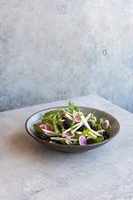 Salad of spinach, fresh greens, blackberries and watermelon radish in a bowl.