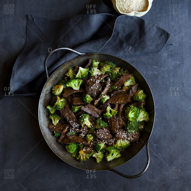 Beef stir fry with broccoli and sesame seeds in a wok
