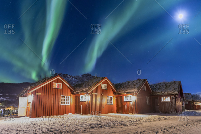 Kafjord, Norway - February 5, 2017: The Northern Lights (aurora borealis) and moon light up typical wood huts called Rorbu, Manndalen, Kafjord, Lyngen Alps