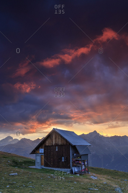 St. Moritz, Switzerland - August 11, 2015: Wooden hut under fiery sky and clouds at sunset, Muottas Muragl, Canton of Graubunden, Engadine