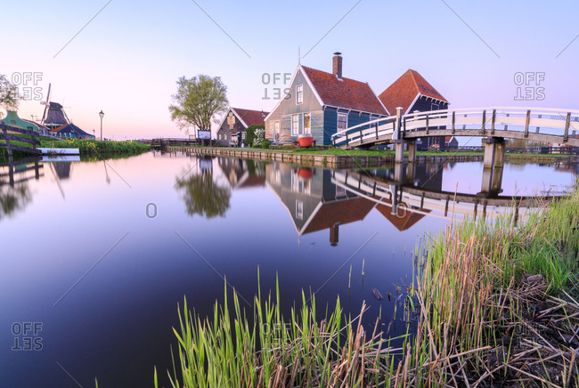 Zaandam, Netherlands - April 8, 2017: Wood houses and windmill reflected in the blue River Zaan at sunset, Zaanse Schans, North Holland, The Netherlands, Europe