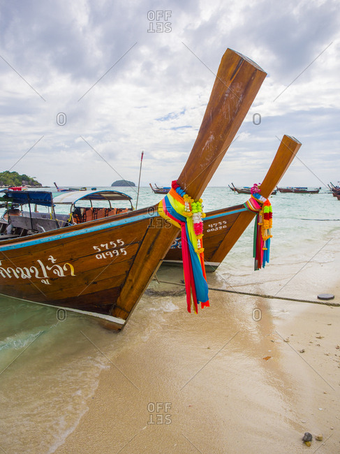 Ko Lipe, Thailand - January 7, 2015: Long-tail boats with coloured-ribbon offerings