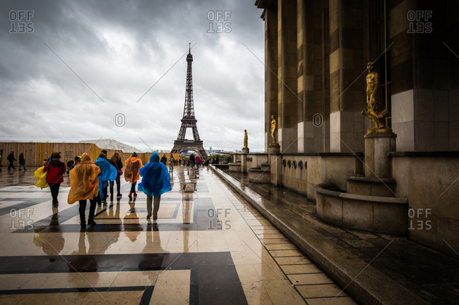 Paris, France - May 3, 2015: Heading towards the Eiffel Tower, tourists brave the rain in colourful ponchos at the Palais De Chaillot