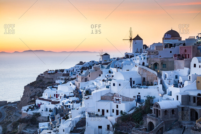 Oia, Greece - June 3, 2016: Sunset view over the whitewashed buildings and windmills of Oia from the castle walls, Santorini, Cyclades, Greek Islands, Greece, Europe