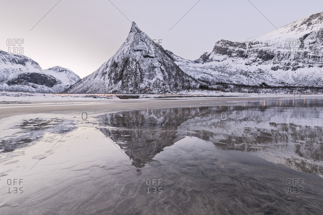 Snowy peaks reflected in the frozen sea surrounded by sandy beach at dawn, Ersfjord, Senja, Troms, Norway, Scandinavia, Europe