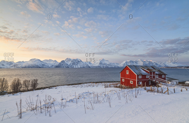Pink sky at sunset on a wooden hut called Rorbu, frozen sea and snowy peaks, Djupvik, Lyngen Alps, Troms, Norway, Scandinavia, Europe