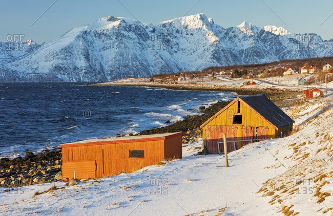 Typical wooden huts called Rorbu surrounded by waves of the cold sea and snowy peaks, Djupvik, Lyngen Alps, Troms, Norway, Scandinavia, Europe