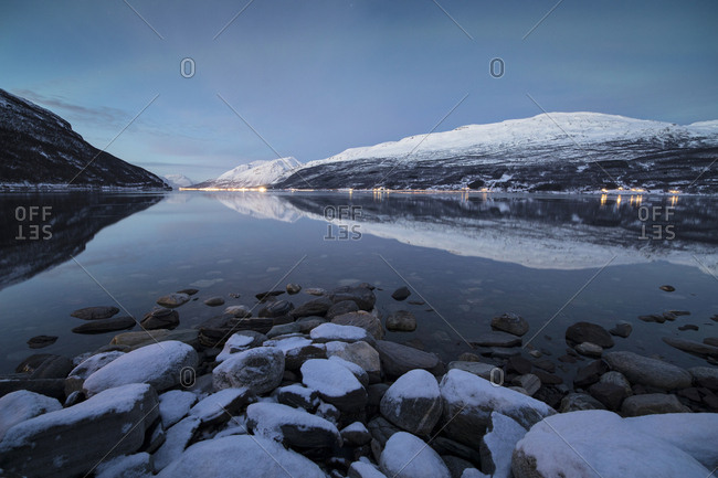 Snowy peaks reflected in the cold sea at dusk, Manndalen, Kafjord, Lyngen Alps, Troms, Norway, Scandinavia, Europe
