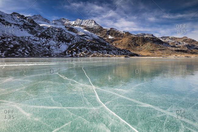 The snowy peaks frame the frozen turquoise water of White Lake (Lago Bianco), Bernina Pass, Canton of Graubunden, Engadine, Switzerland, Europe