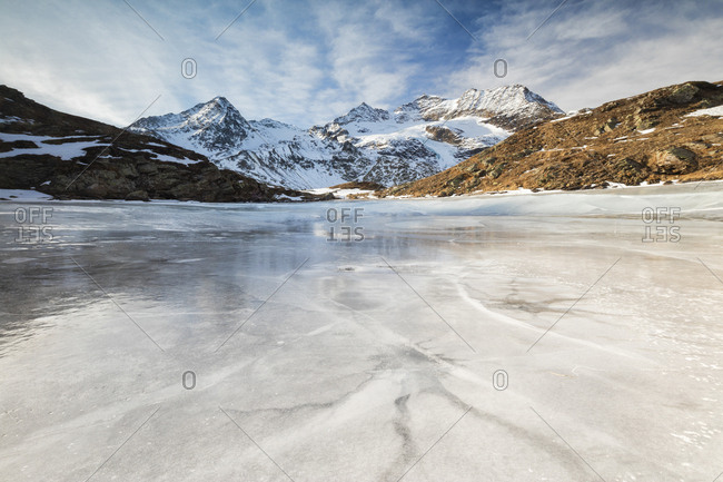 Blue sky and clouds on frozen Lej Nair surrounded by snowy peaks, Bernina Pass, Canton of Graubunden, Engadine, Switzerland, Europe