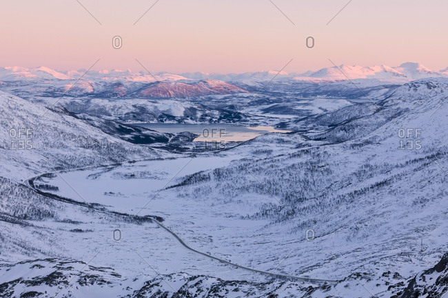 Pink sky at sunset on the snowy landscape and frozen sea surrounding Fjordbotn, Lysnes, Senja, Troms, Norway, Scandinavia, Europe