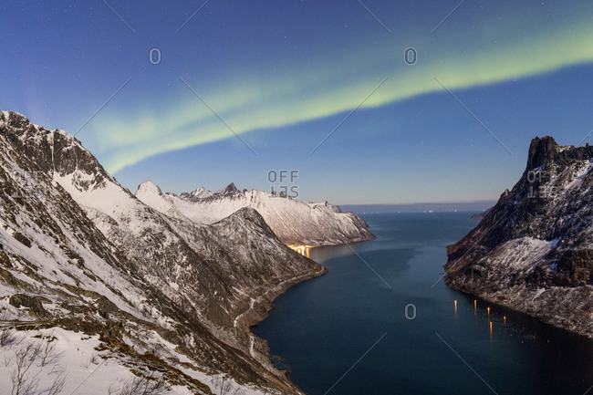 Northern Lights (aurora borealis) on the snowy peaks and the village of Fjordgard framed by the frozen sea, Ornfjorden, Senja, Troms, Norway, Scandinavia, Europe
