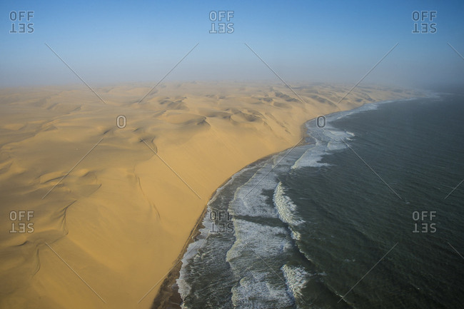 Aerials of sand dunes of the Namib Desert meeting the Atlantic Ocean, Namibia, Africa