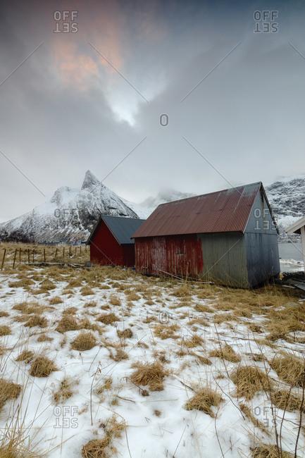 Clouds on snowy peaks above typical wooden hut called Rorbu, Senja, Ersfjord, Troms county, Norway, Scandinavia, Europe
