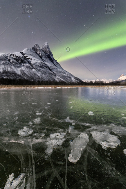 Ice bubbles of frozen sea and the snowy peak of Otertinden under the Northern Lights (aurora borealis), Oteren, Lyngen Alps, Troms, Norway, Scandinavia, Europe