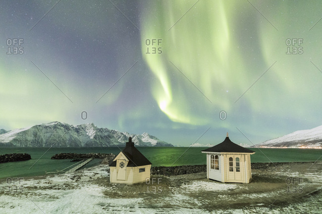 The Northern Lights (aurora borealis) and stars illuminate the wooden huts by icy sea, Djupvik, Lyngen Alps, Troms, Norway, Scandinavia, Europe