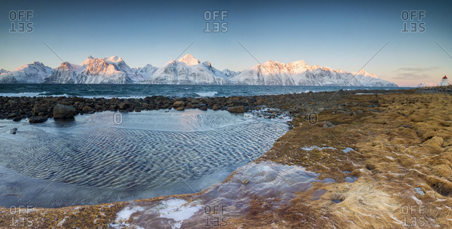 Panorama of frozen sea and snowy peaks at dawn surrounded by rocks covered with ice, Djupvik, Lyngen Alps, Troms, Norway, Scandinavia, Europe
