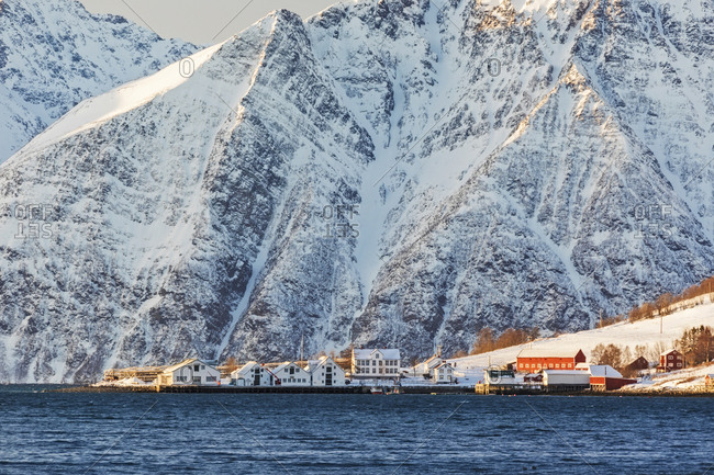 The typical fishing village of Hamnes framed by snowy peaks and the cold sea, Lyngen Alps, Troms, Norway, Scandinavia, Europe