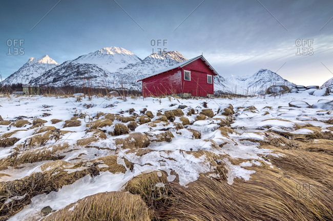 Wood hut framed by rocks covered with grass and ice with snowy peaks in the background, Svensby, Lyngen Alps, Troms, Norway, Scandinavia, Europe