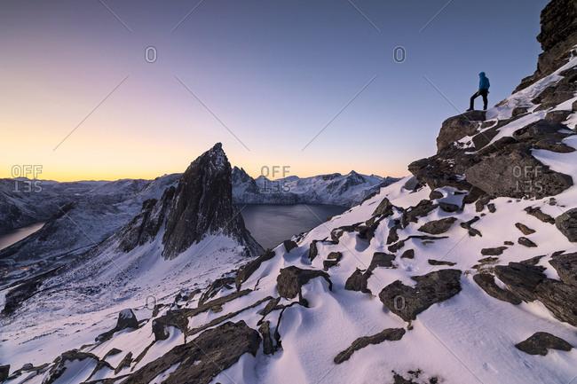 Hiker on peak Hesten admires Mount Segla and the Mefjorden framed by frozen sea at sunrise, Senja, Troms, Norway, Scandinavia, Europe