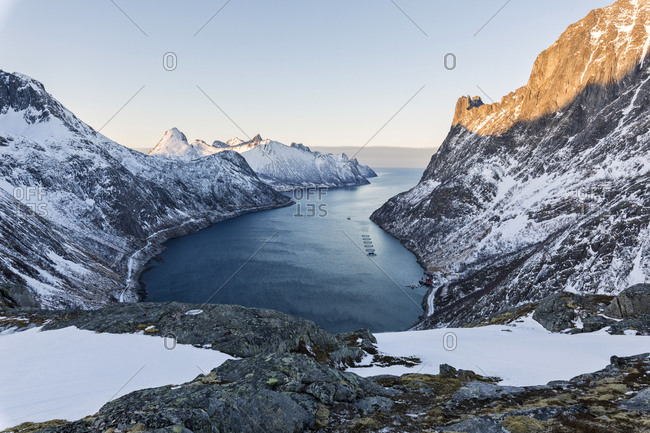 Panorama of peaks of the Ornfjorden framing the village of Fjordgard and Mount Segla in background, Senja, Troms, Norway, Scandinavia, Europe