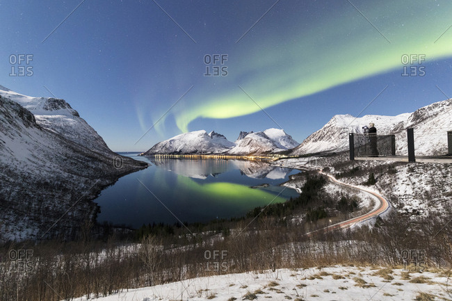 Photographer on platform admires the Northern lights (aurora borealis) and stars reflected in the cold sea, Bergsbotn, Senja, Troms, Norway, Scandinavia, Europe
