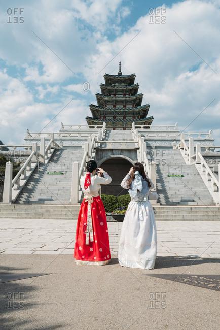 Seoul, South Korea - May 21, 2017: Women wearing traditional Korean dresses taking photos of the National Folk Museum of Korea- inside Gyeongbokgung Palace