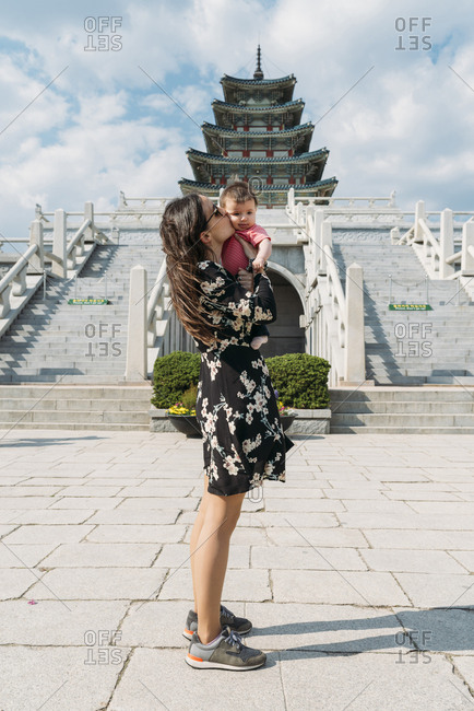 Seoul, South Korea - May 21, 2017: Woman holding and kissing a baby girl in front of the National Folk Museum of Korea- inside Gyeongbokgung Palace