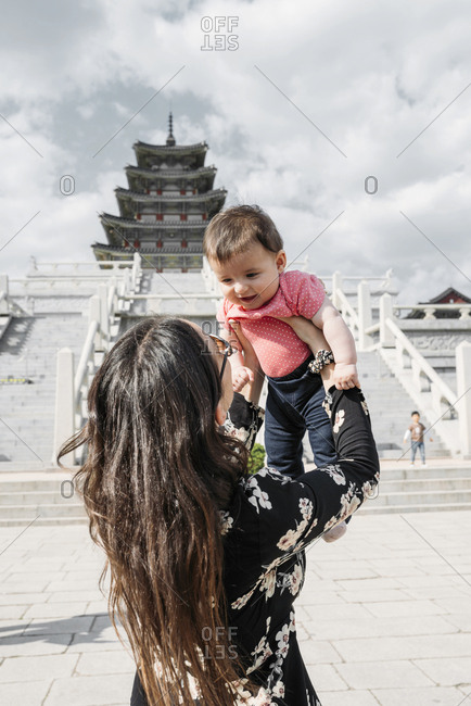 Seoul, South Korea - May 21, 2017: Woman holding a baby girl in front of the National Folk Museum of Korea- inside Gyeongbokgung Palace