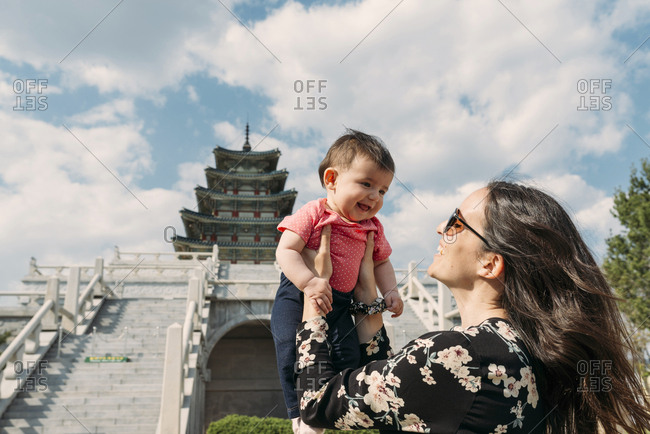 Seoul, South Korea - May 21, 2017: Happy woman holding a baby girl in front of the National Folk Museum of Korea- inside Gyeongbokgung Palace