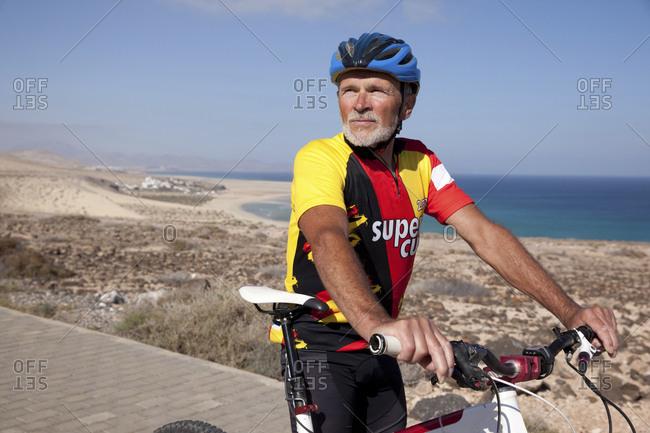 Canary Islands, Spain - April 6, 2017: Fuerteventura- senior man with mountain bike having a rest