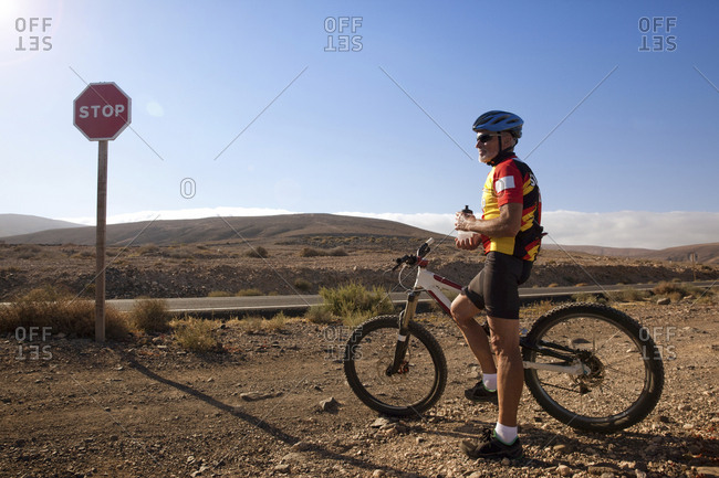 Canary Islands, Spain - April 6, 2017: Fuerteventura- senior man with mountain bike having a rest