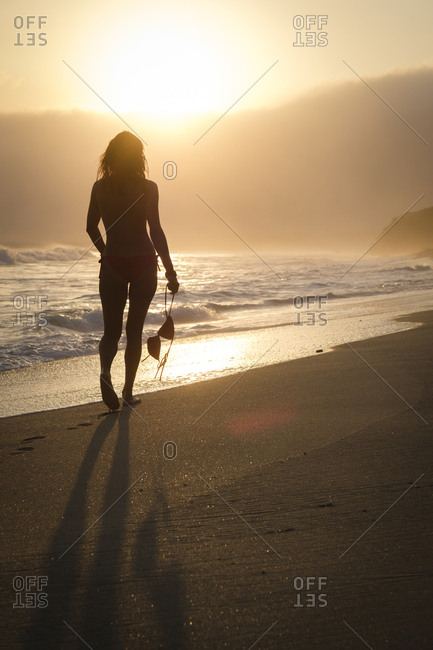 Mexico- Riviera Nayarit- silhouette of woman walking into the sunset at a beach while holding her bikini top