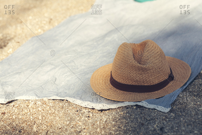 Straw hat on cloth on sandy beach