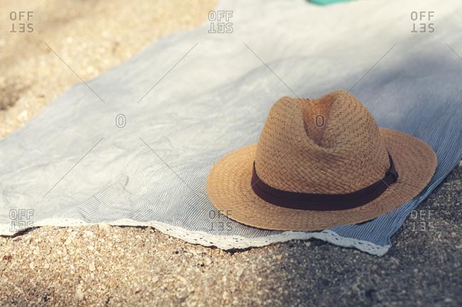 Straw hat on cloth on sandy beach