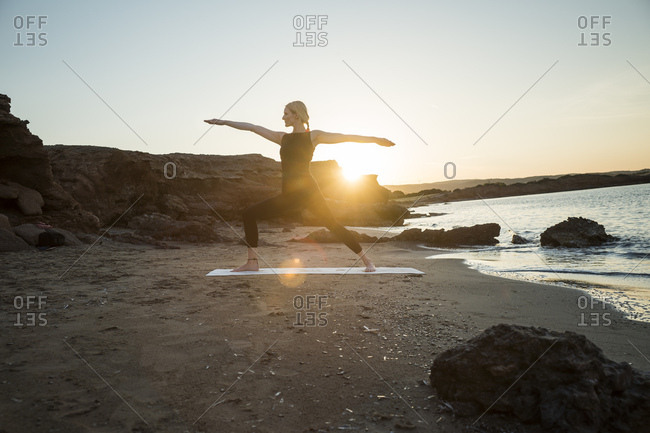 Greece- Crete- woman practicing yoga on the beach at sunset