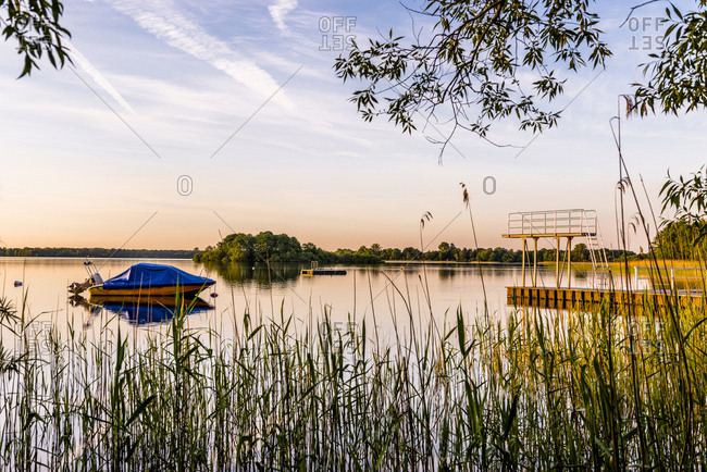Germany- Schaalsee with moored motorboat and highboard at evening twilight