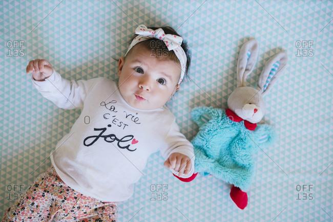 Baby girl lying on bed beside toy bunny