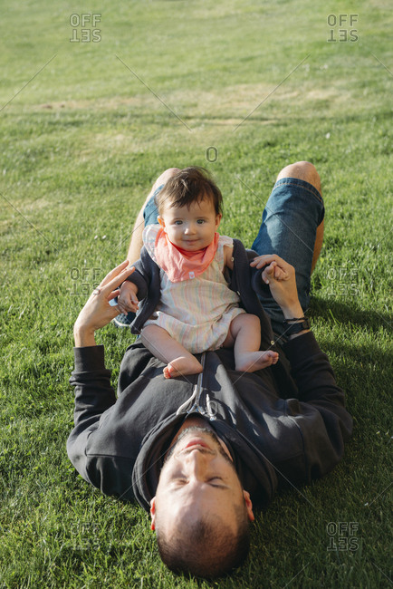 Cute baby girl sitting on her father's belly in a meadow