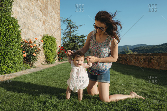 Cute baby girl walking on the grass with the help of her mother