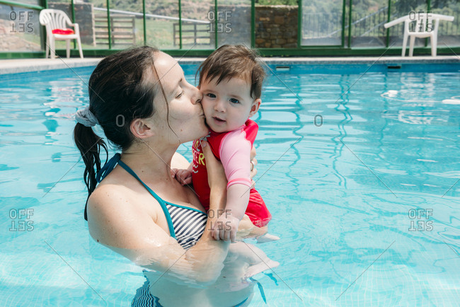 Mother kissing her baby girl in swimming pool