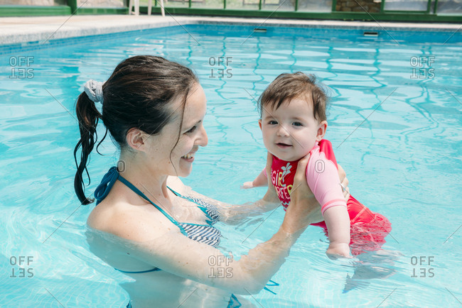 Cute baby girl learning to swim in the pool with her mother