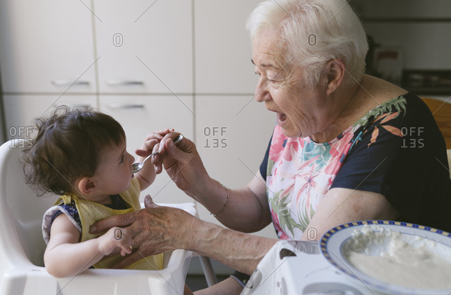 Grandmother feeding baby girl in the kitchen