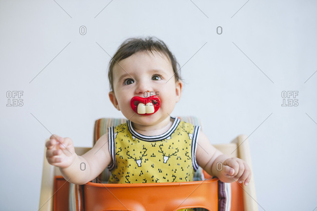 Portrait of baby girl sucking a pacifier with false teeth and mouth