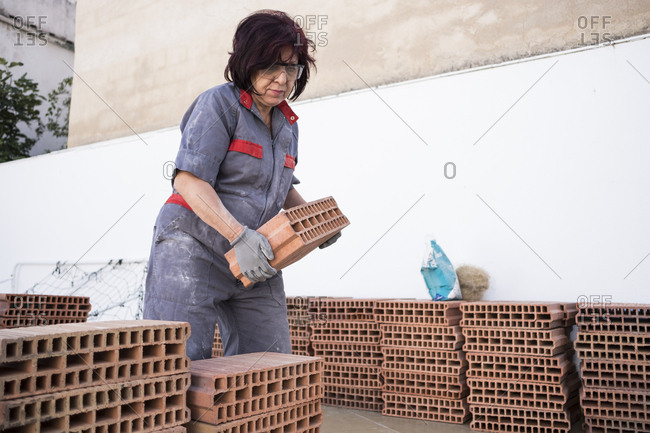 Senior woman piling bricks