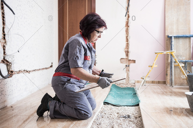 Senior woman laying tiles at construction site