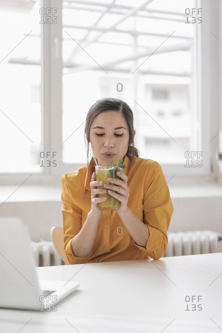 Young woman drinking tea at her desk